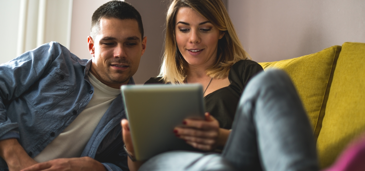 man and woman looking at device on sofa