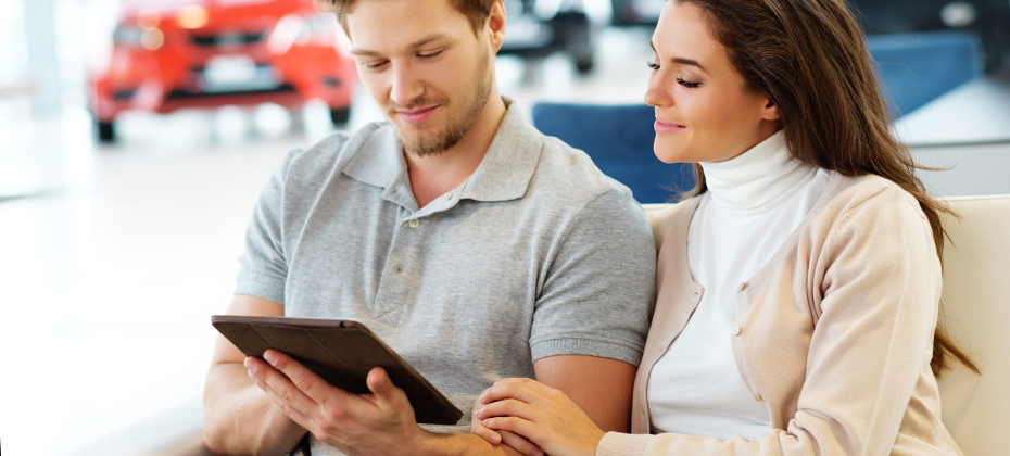 Young couple looking at tablet in car dealership
