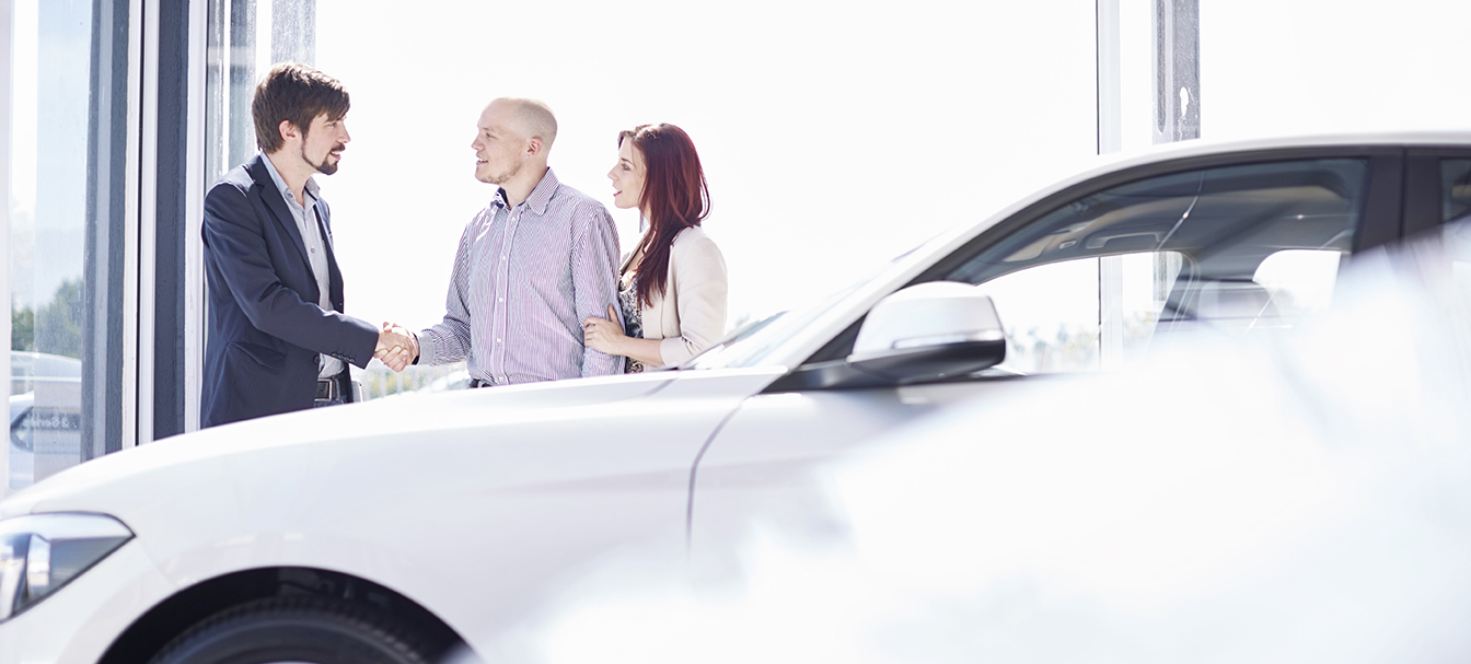 Car dealer with couple in showroom