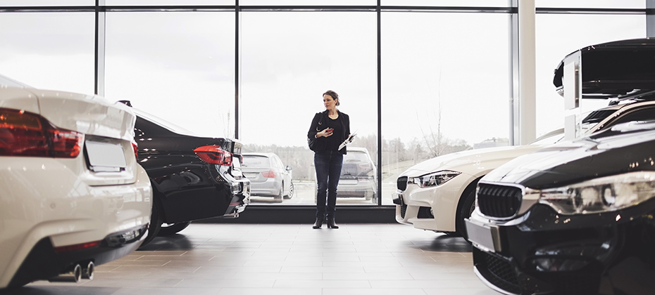 Woman looking at cars in auto dealership