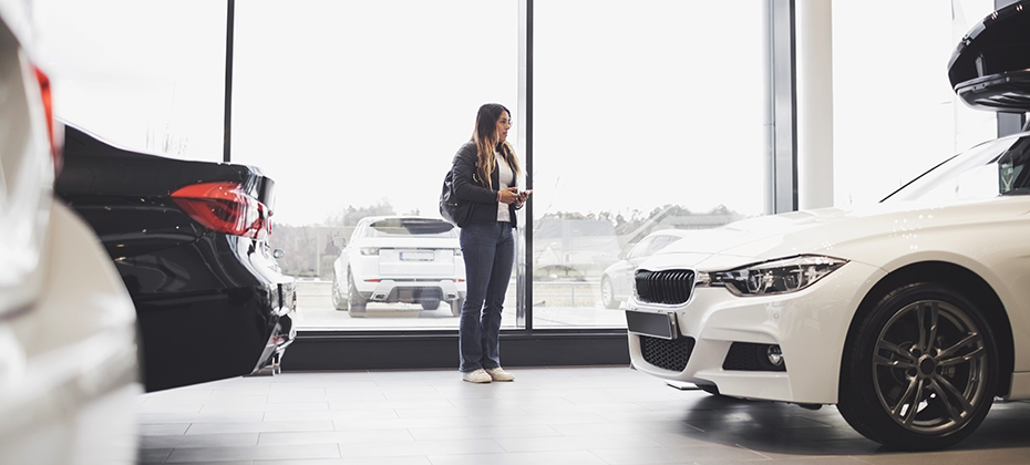 Young woman standing against glass window at car showroom