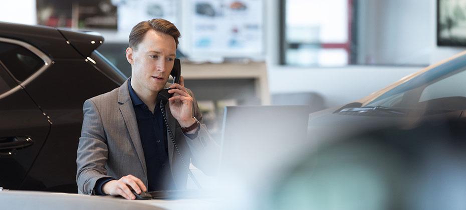 Car salesperson talking on landline phone