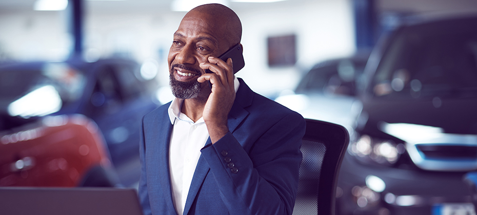 Black man sitting in car dealer showroom on the phone