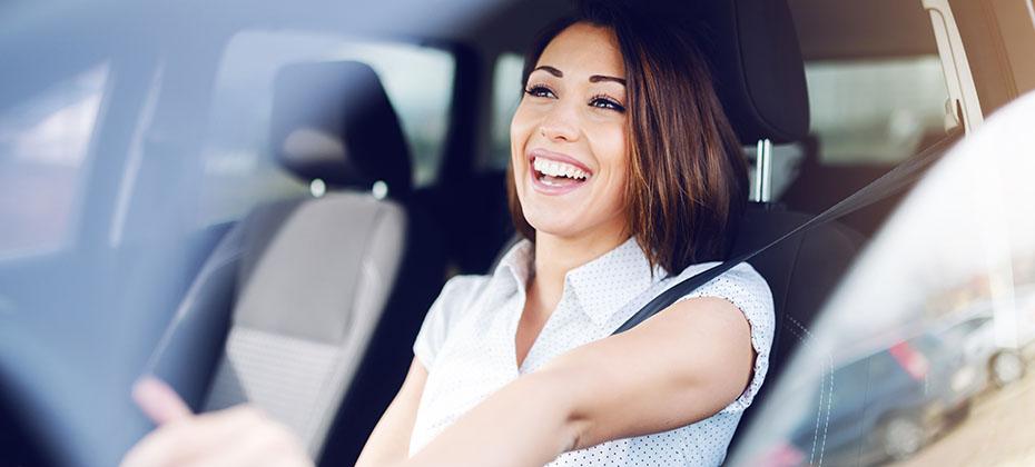 Smiling brunette driving her car. Hands are on steering wheel.