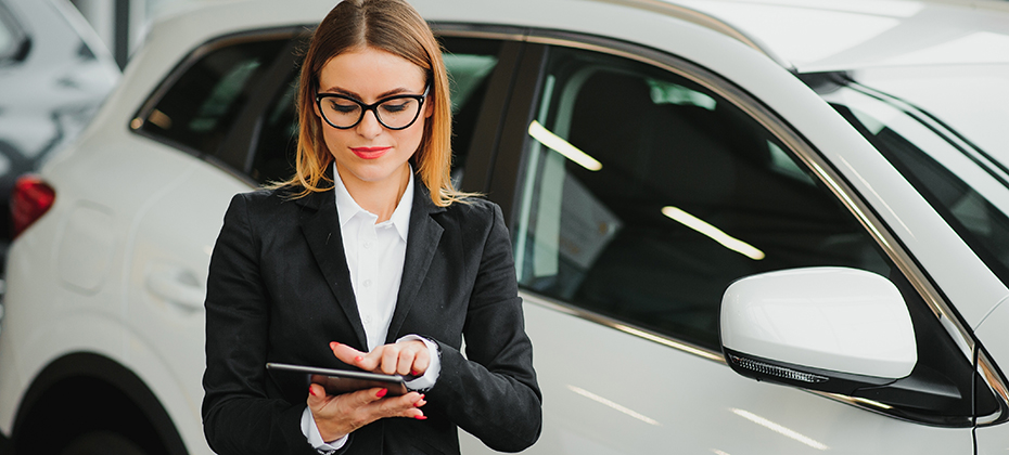 Business woman with tablet in car dealership