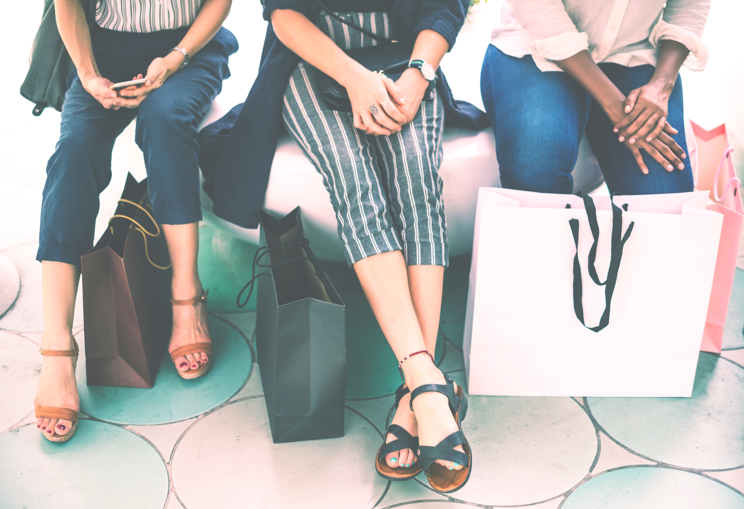 Three woman sit with their hands crossed and shopping bags at their feet