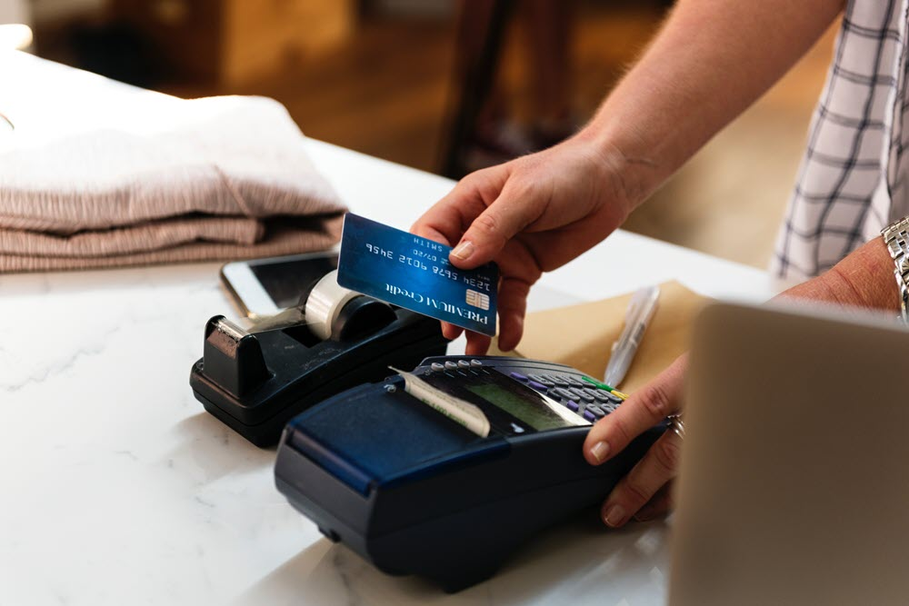Man prepares to insert EMV chip on credit card into card reader at the register