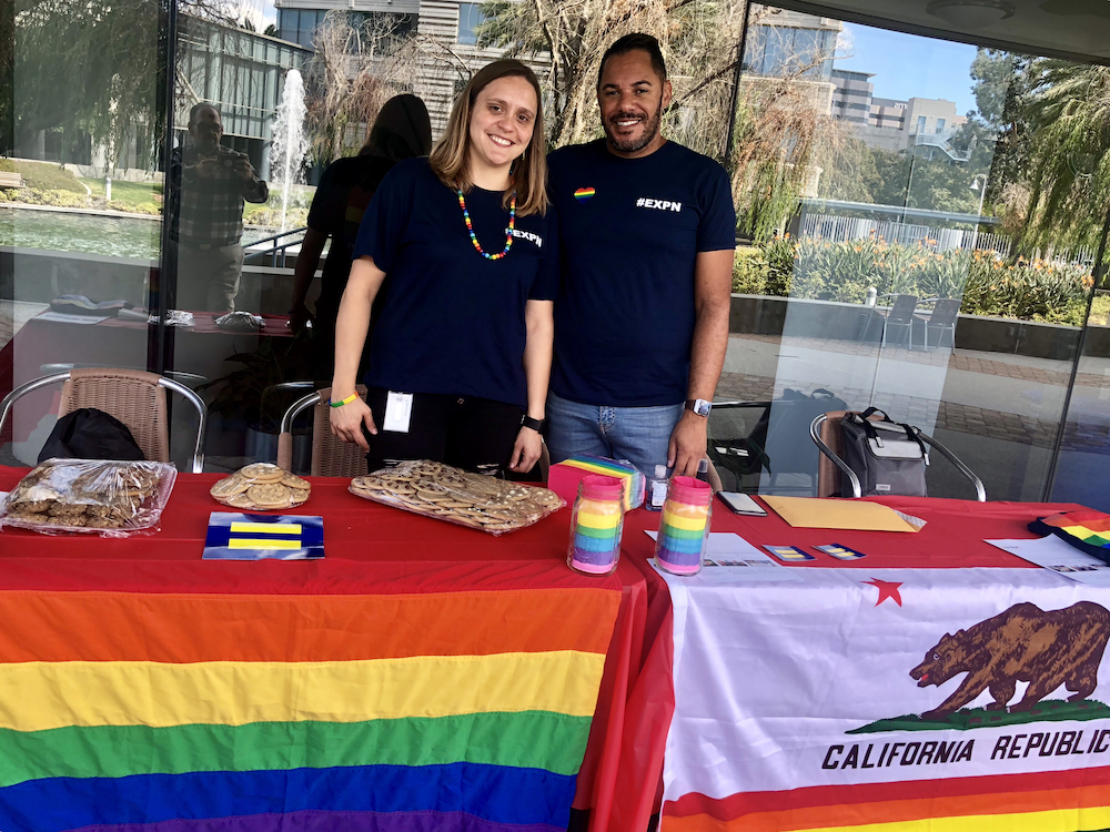 Two Pride Network members pose behind their information tables, which are draped with the rainbow flag