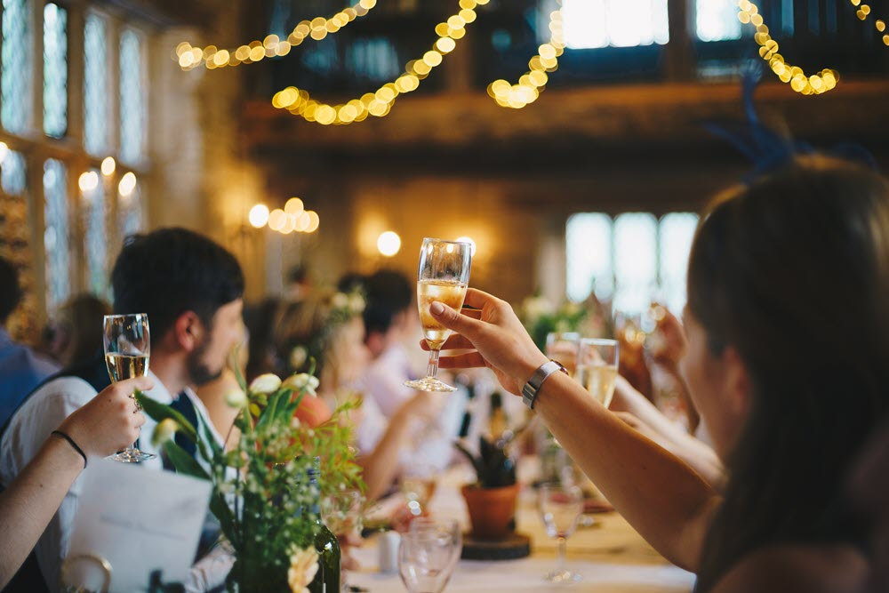 Party-goers raise their glasses of champagne to toast at a Christmas party
