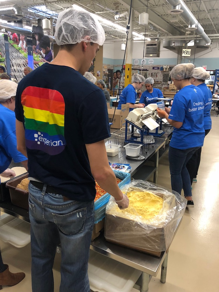 A man wearing a rainbow Pride Network shirt volunteers at a kitchen with a hair net on