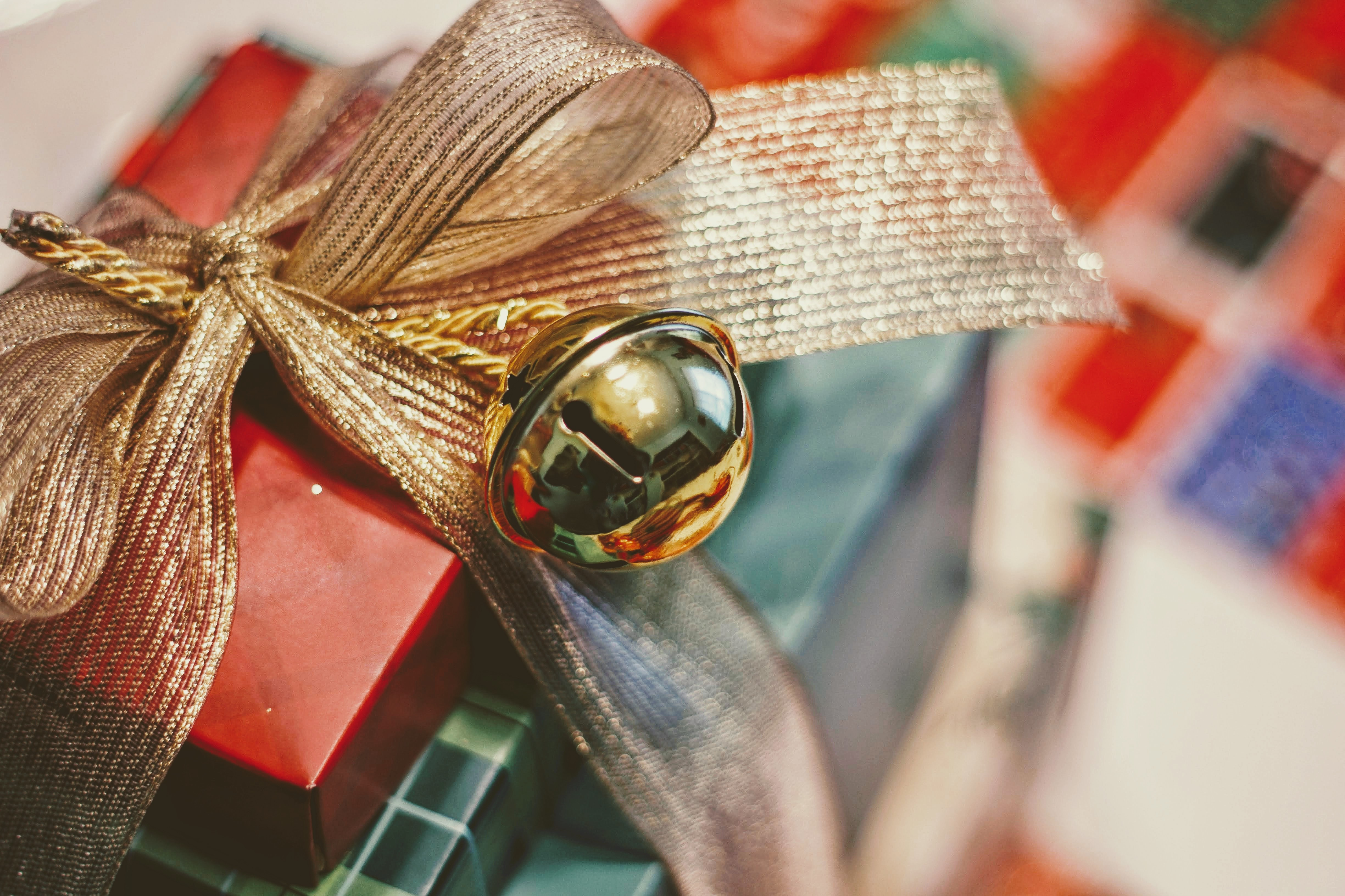 Christmas gifts wrapped in red and plaid paper, tied into a three-tier stack with a golden bell tied to the bow