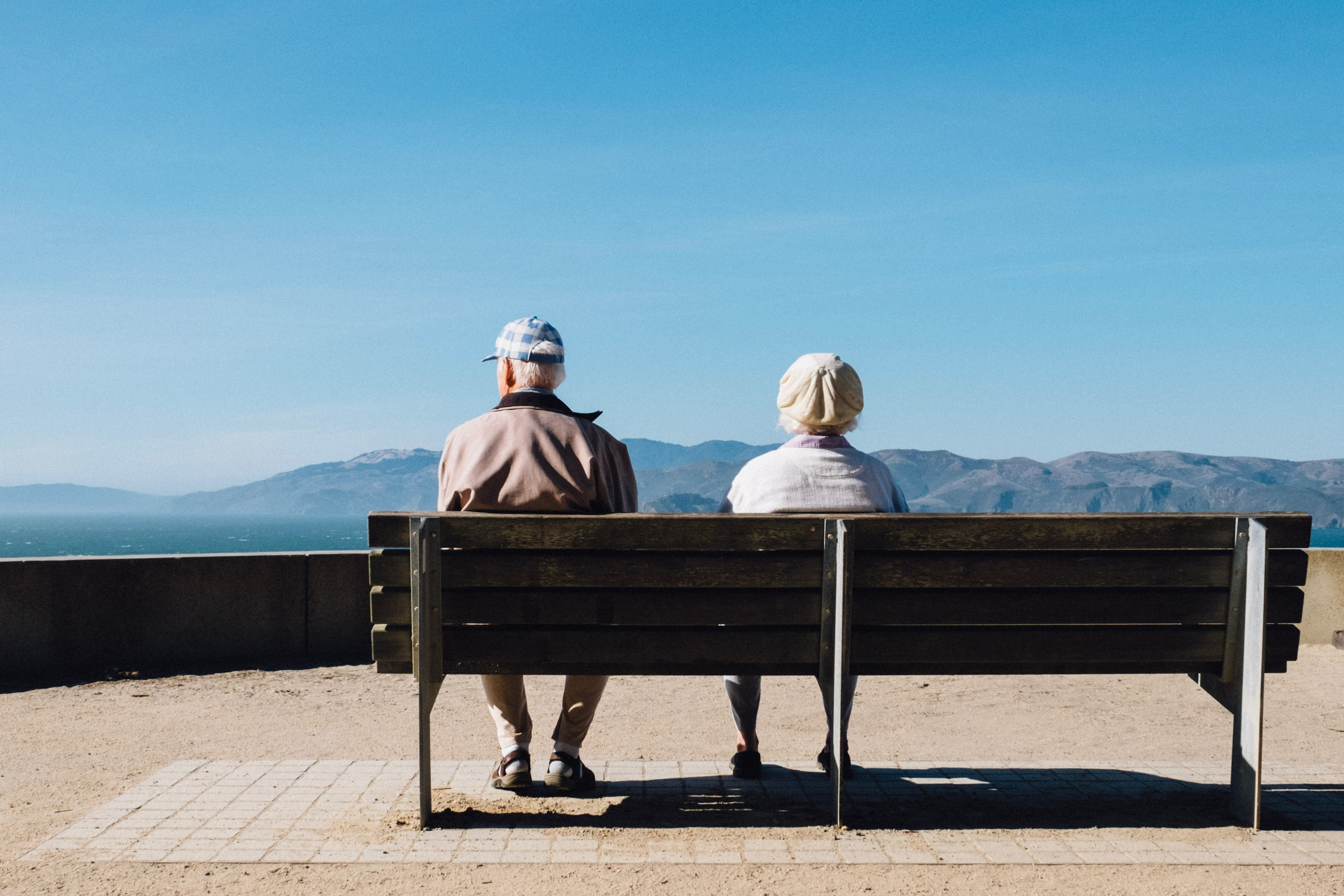 Older couple sits on a bench and enjoys the view of the mountains and blue sky