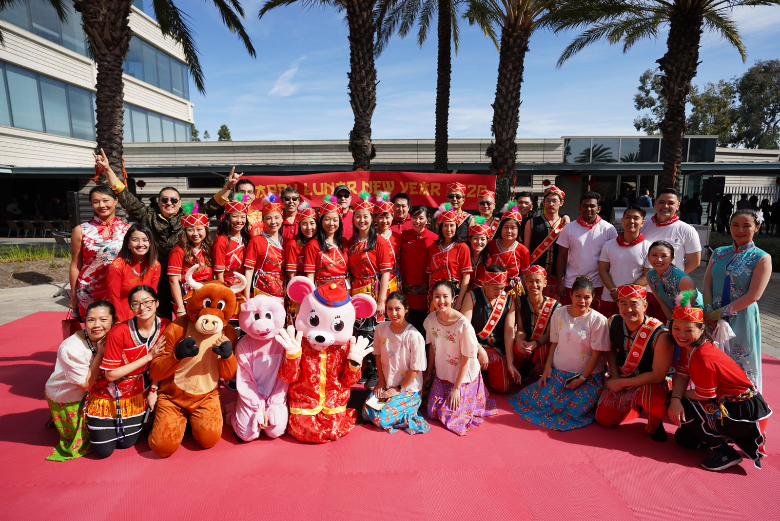 Experian's Asian American ERG in traditional clothing, posing together with Year of the Rat mascot