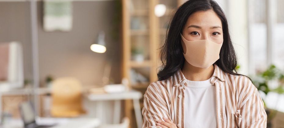 Young Asian woman wearing mask and looking a camera while standing with arms crossed in modern office