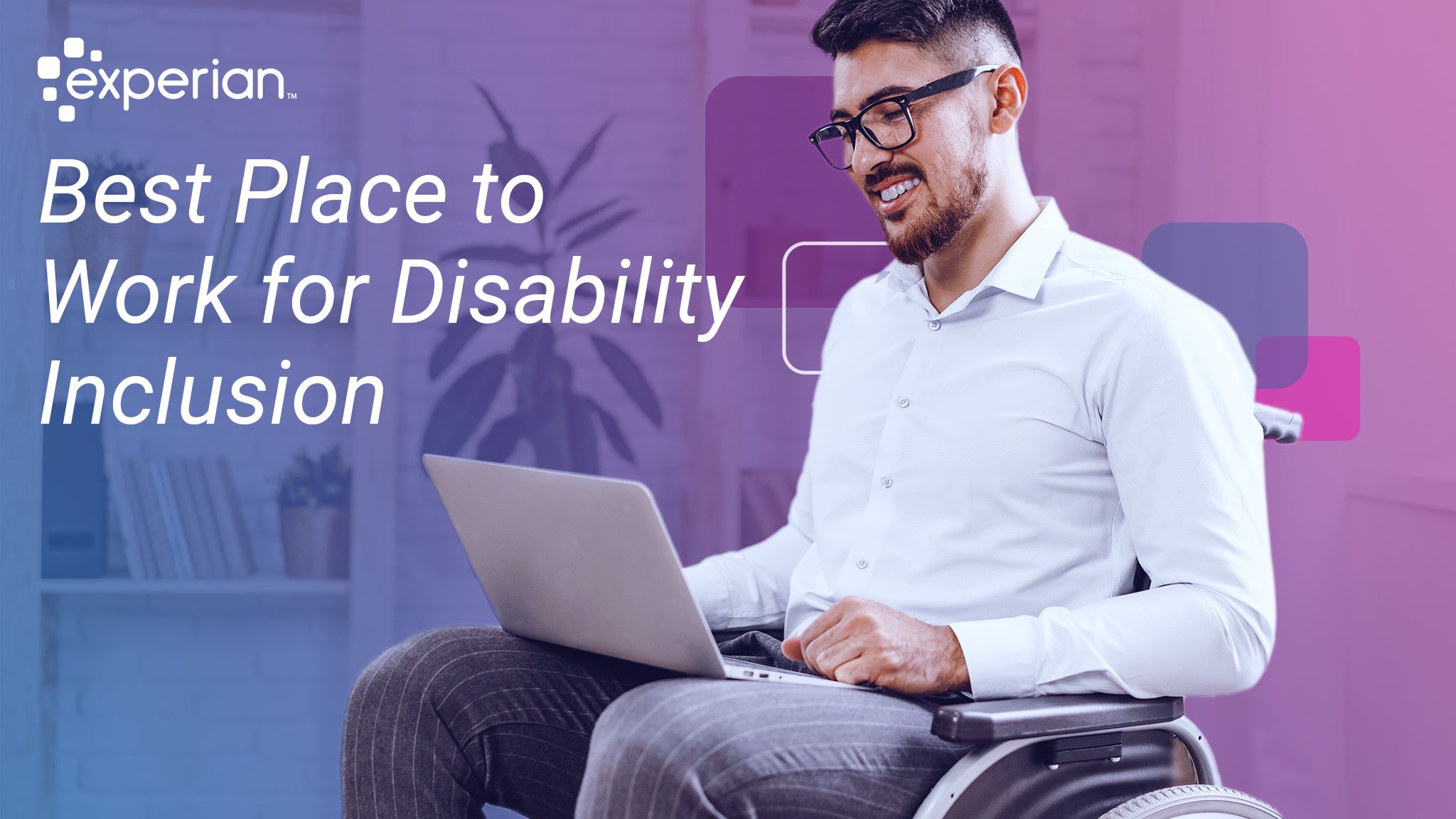 Man in a wheelchair smiles while working on his laptop.