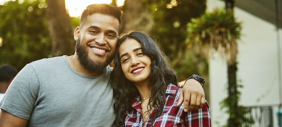 Latinx smiling friends. Young males and females are wearing casuals. They are in back yard.