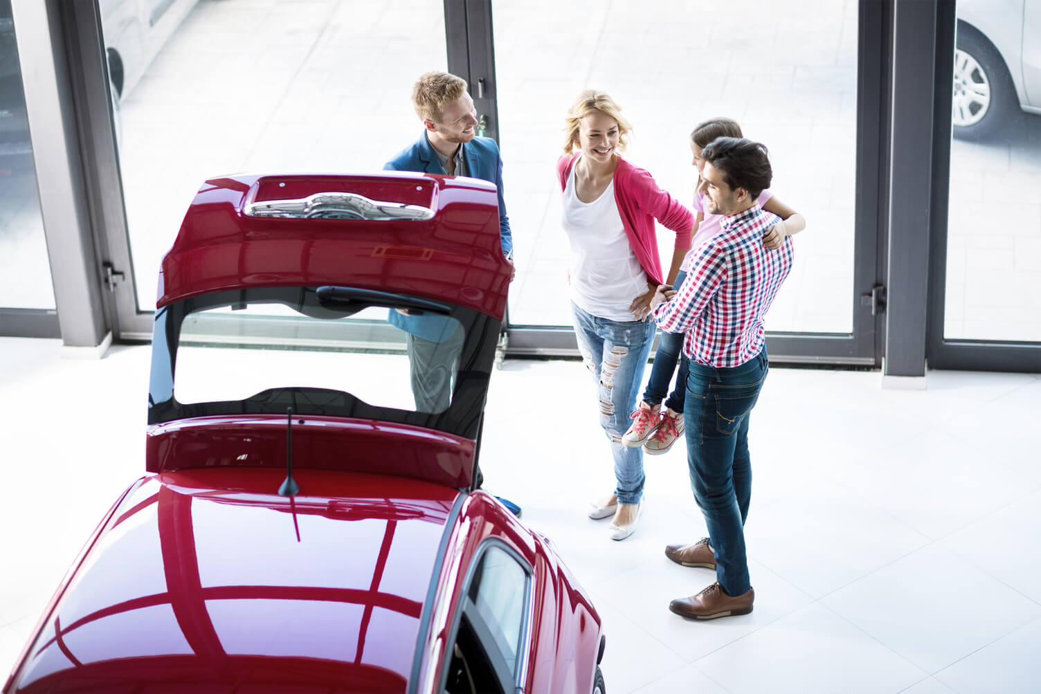 Three people admiring the the carrying capacity of a car on the showroom floor.