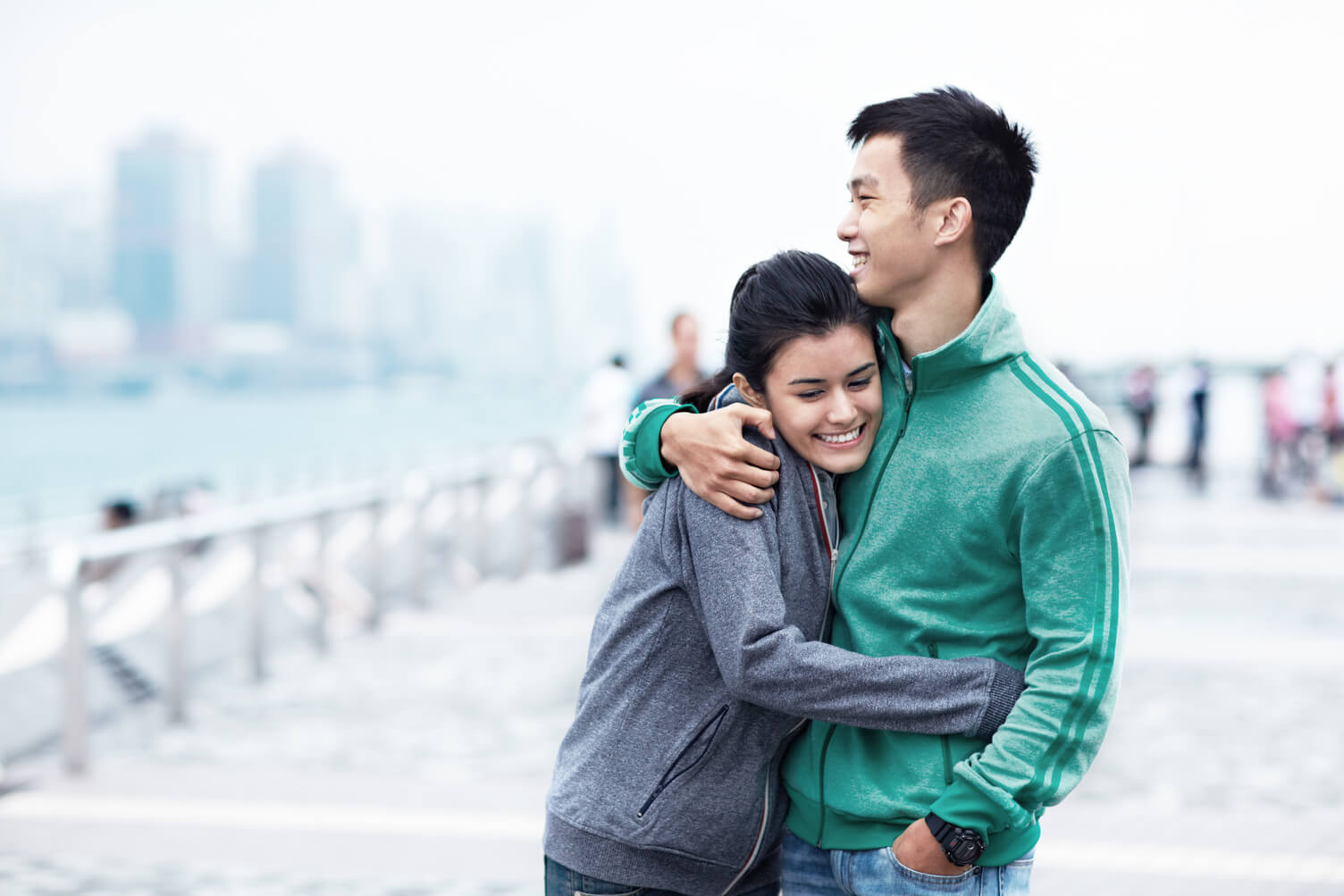 Young couple hugging and smiling.