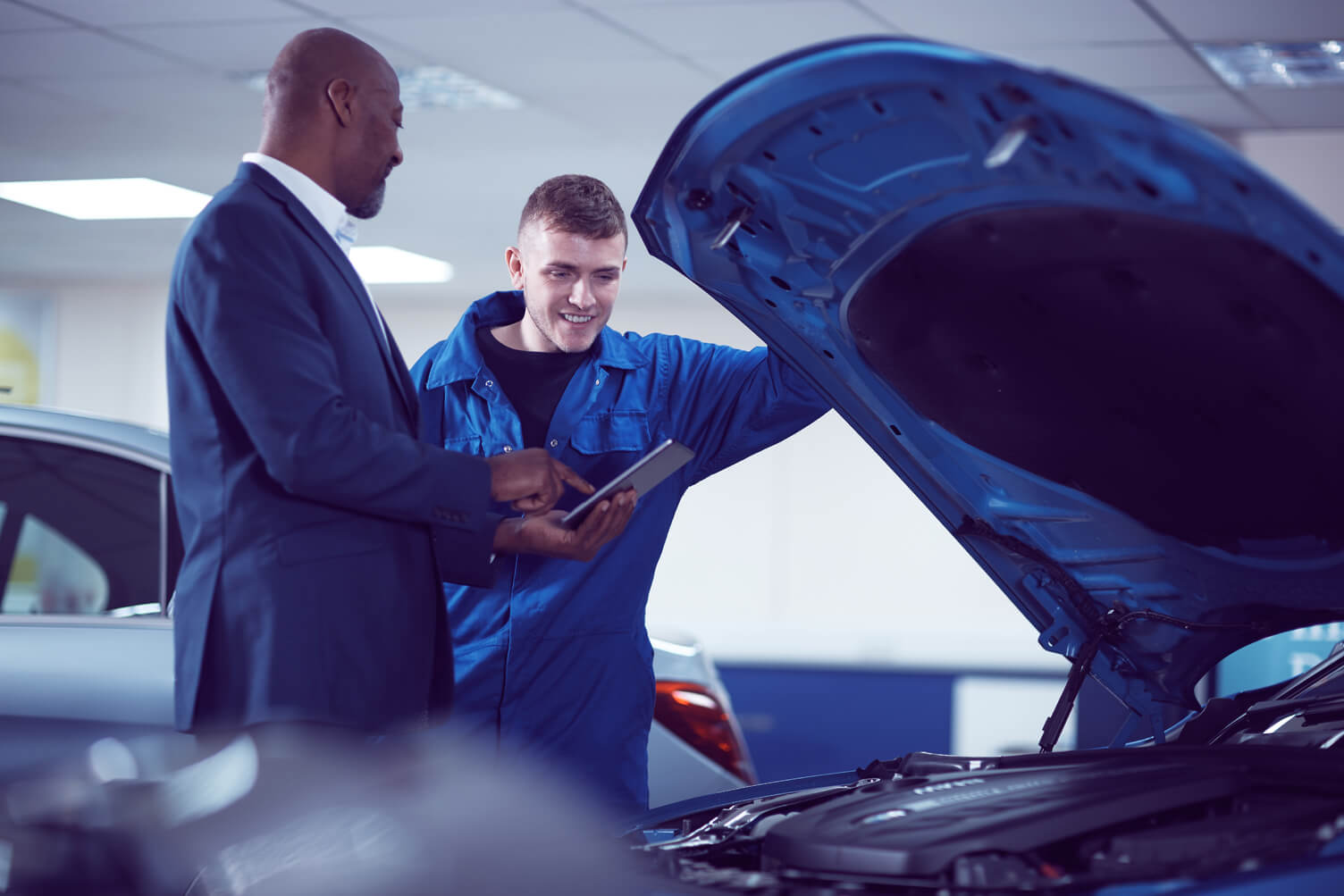 Two men looking under the hood of a car