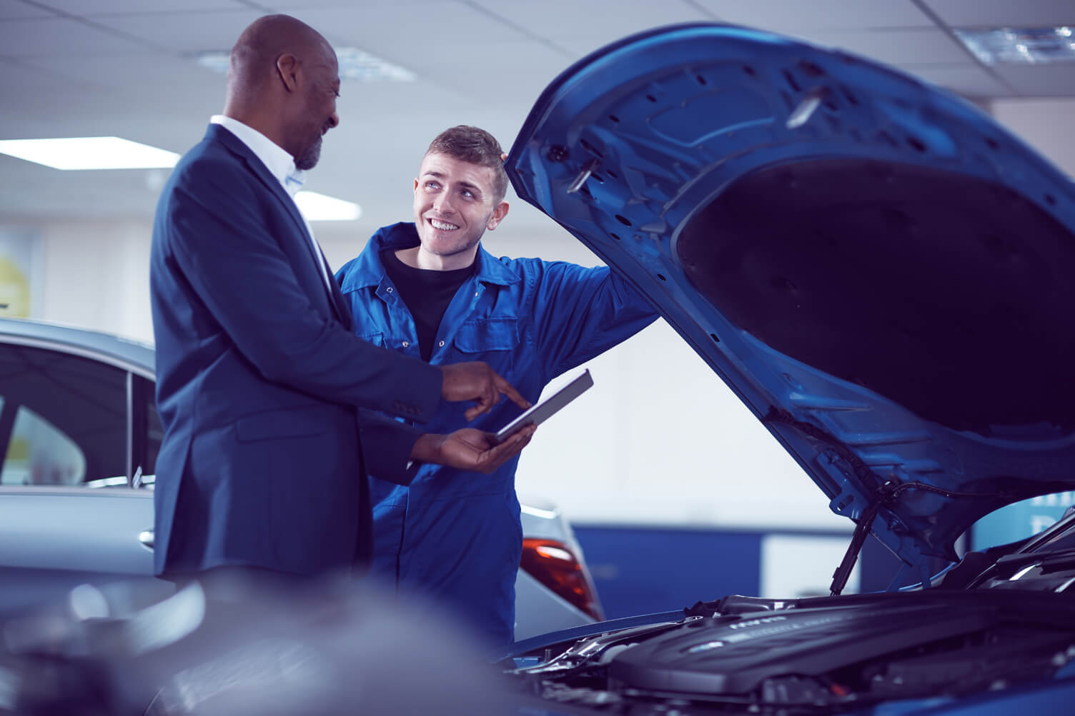 Customer and mechanic looking under the hood of a car.